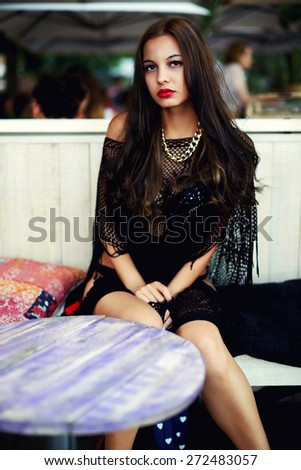 Fashionable young woman with red lips dressed in black swimsuit posing to the camera, gorgeous female with brunette long hair sitting at beach cafe, charming model in bikini at perfect summer days - stock photo
