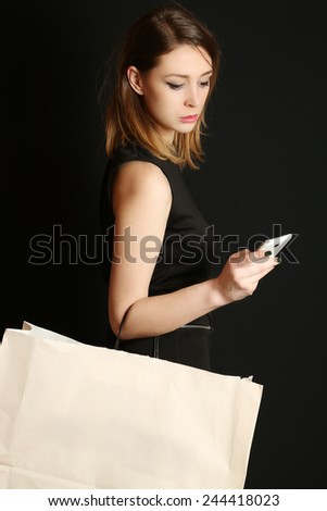 Fashionable young woman with shopping bag, Attractive woman using a smartphone and holding blank shopping bag - stock photo