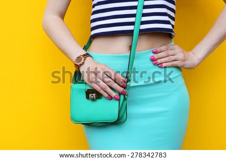 Fashionable young woman with small green handbag close up . Outdoor trendy outfit blue skirt with striped top - stock photo