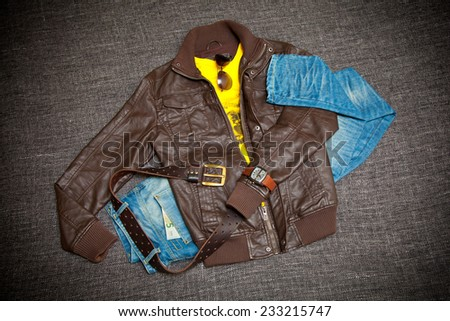 Fashionable youth clothes: leather jacket, jeans with a belt, shirt, watches and sunglasses - stock photo