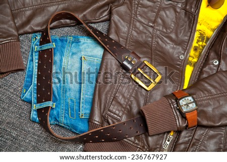 Fashionable youth clothes. Leather jacket, T-shirt, jeans, a leather belt with a buckle, sunglasses, watches - stock photo