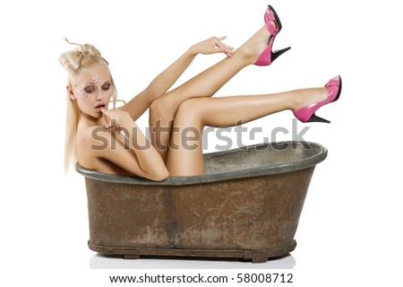 fashions shot of sexy blond girl pin up with a nice creative make up and hair styling in an old little bath - stock photo