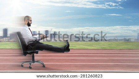 Fast business - businessman sitting with laptop runs on track  - stock photo