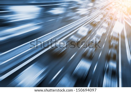 fast cars on freeway, sunlight in background - stock photo