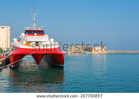 Fast catamaran ferry moored  in port of Heraklion. Venetian Fortress of Rocca al Mare in the background. Crete, Greece, Europe - stock photo