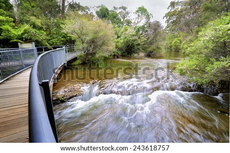 Fast flowing water on the approach to Fitzroy Falls.   A timber and steel walking bridge allows visitors to traverse both sides of the escarpment - stock photo