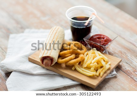 fast food and unhealthy eating concept - close up of deep-fried squid rings, french fries, coca cola and ketchup on wooden table - stock photo