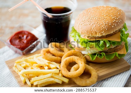 fast food and unhealthy eating concept - close up of hamburger or cheeseburger, deep-fried squid rings, french fries, cola drink and ketchup on wooden table - stock photo