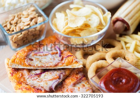 fast food and unhealthy eating concept - close up of pizza, deep-fried squid rings, potato chips, peanuts and ketchup on wooden table top view - stock photo