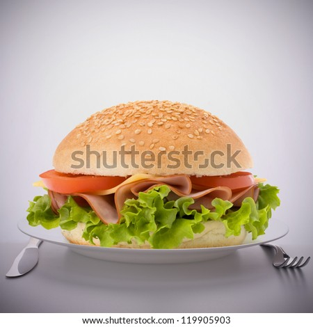 Fast food big sandwich with lettuce, tomato, smoked ham and cheese on plate - stock photo