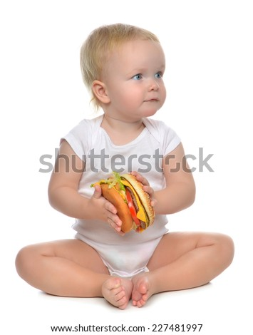 Fast food concept. Infant child baby toddler hold tasty unhealthy burger sandwich in hands hungry getting ready to eat isolated on a white background - stock photo