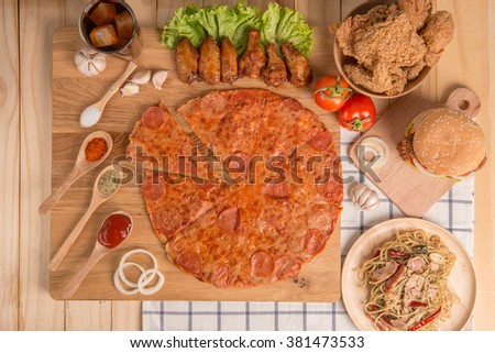 Fast food concept with fried chicken , pizza , burger and spaghetti as a symbol of diet temptation resulting in unhealthy nutrition - stock photo