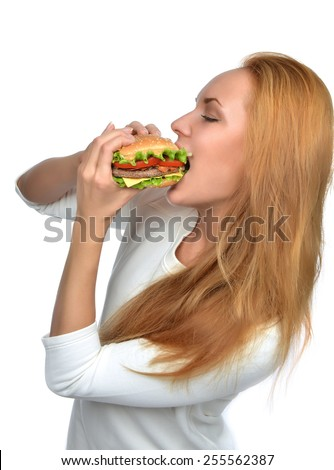 Fast food concept. Woman eating tasty unhealthy burger sandwich in hands hungry mouth getting ready to eat isolated on a white background - stock photo