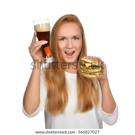 Fast food concept. Woman hold tasty unhealthy burger sandwich in hand and bottle of beer hungry getting ready to eat drink smiling yelling isolated on a white background - stock photo