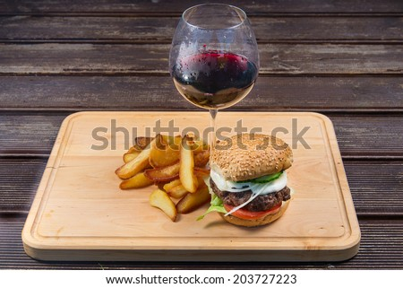 Fast food hamburger and french fries on a wooden plate. and glass of red wine  - stock photo