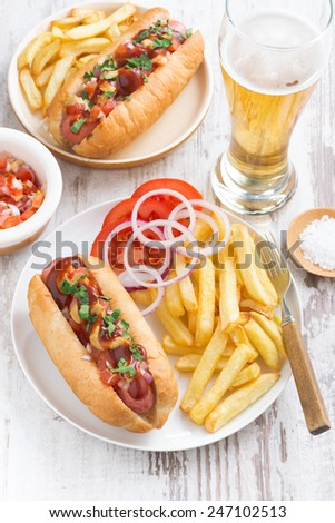 fast food - hot dog with French fries, beer and snacks on wooden table, top view, vertical - stock photo