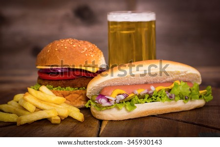 Fast food - Hot dogs, hamburger and French fries  - stock photo