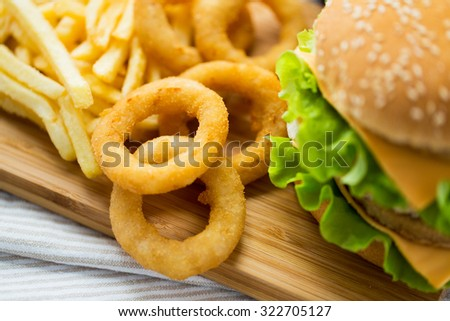 fast food, junk-food and unhealthy eating concept - close up of hamburger or cheeseburger, deep-fried squid rings and french fries on wooden table - stock photo