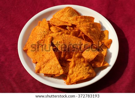 Fast food, junk-food/close up of corn nachos in plate on red background. - stock photo