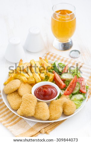 fast food lunch with chicken nuggets, french fries and vegetable salad, vertical - stock photo