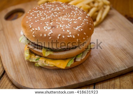 Fast food set big hamburger and french fries on wood background - stock photo