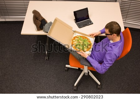fast meal in office - man sitting at with legs on the desk, heaving break for pizza  - stock photo