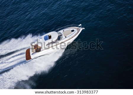 Fast motor boat on blue ocean shot from above in helicopter - stock photo