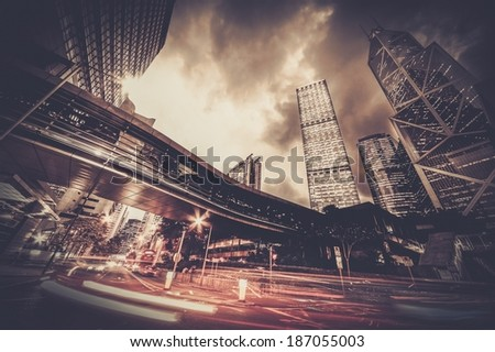 Fast moving cars at night in modern city - stock photo