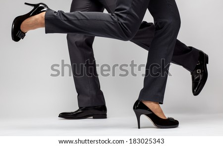 Fast-paced business: male and female legs running on grey background - stock photo