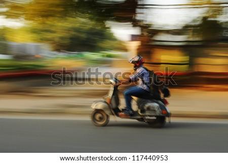 Fast riding motorbike, emotional blurred image, Old Delhi, India - stock photo