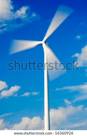 Fast spinning wind turbine and blue sky with few clouds (rotor with strong motion blur) - stock photo