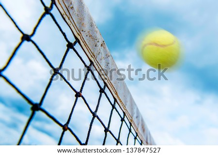 Fast tennis ball going over the net at full speed - stock photo