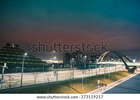 Fast traffic in a road and bridge in modern and futuristic city by night - stock photo
