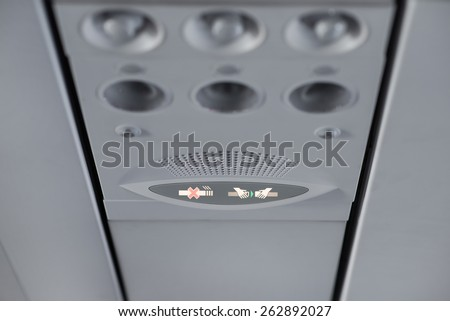 Fasten seat belt and no smoking signs in aircraft - stock photo