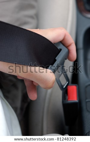 Fastening the seatbelt in the car. - stock photo