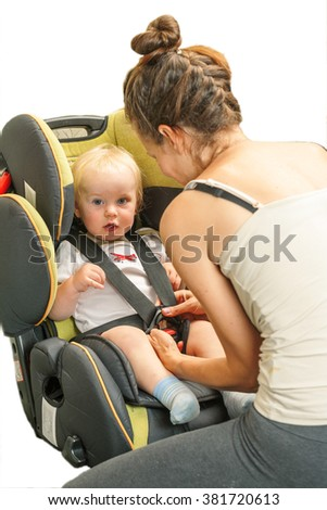 fastens the baby car seat in the mother. the baby is crying - stock photo