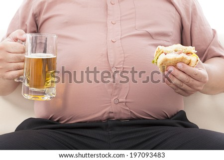 fat business man holding beer mug and hamburger - stock photo