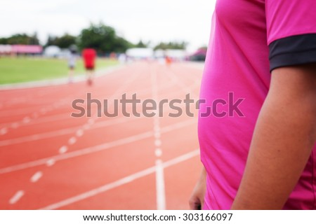 Fat man athlete is at the start of the treadmill at the stadium - stock photo