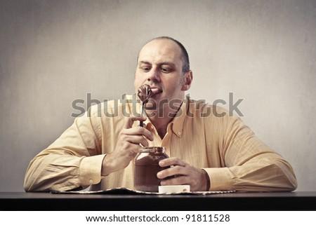 Fat man eating chocolate cream - stock photo