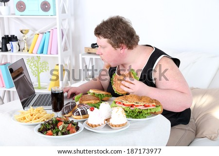 Fat man has a big lunch and playing games on laptop, on home interior background   - stock photo
