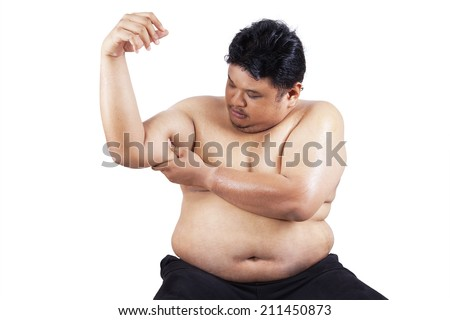 Fat man holding his flabby biceps, isolated on white background - stock photo