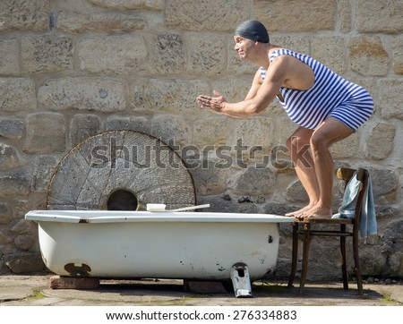 Fat man in retro swimsuit jumps to the outdoor bathtub. Funny swimmer in vintage style and bathing cap starts to swim in the tub. Home vacations. Domestic holiday. - stock photo