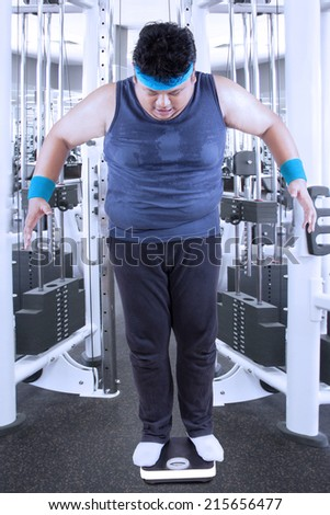 Fat man measuring his weight in the fitness center - stock photo