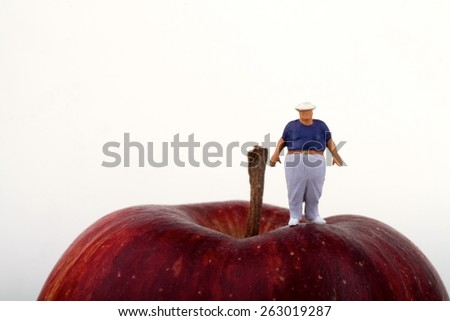 Fat man on The top of a Red Apple - obesity concept - stock photo