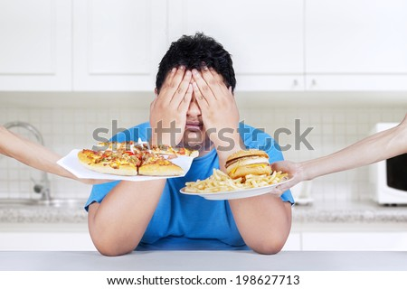 Fat man rejecting to eat junk food. Shoot at home in the kitchen - stock photo