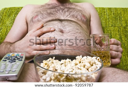 Fat man with glass of beer and popcorn - stock photo