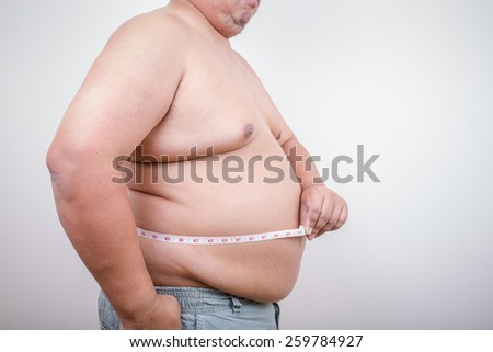 Fat mature man measuring his belly with measurement tape, isolated on white background - stock photo