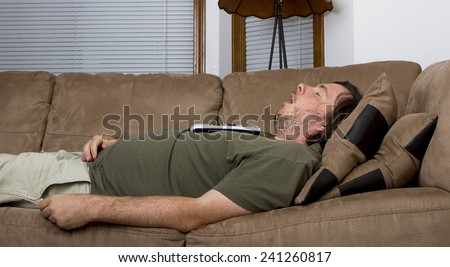 Fat obese man fell asleep on the couch with a remote on his chest - stock photo