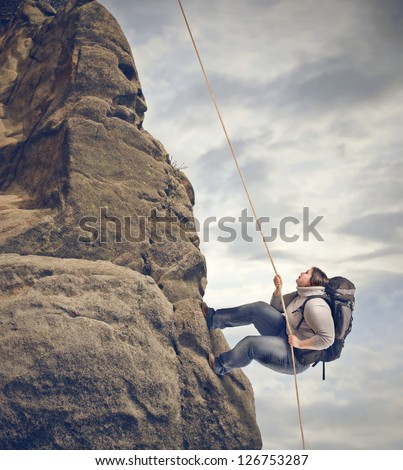 fat woman climbing a mountain with rope - stock photo