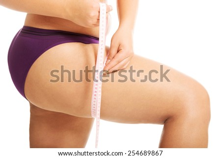 Fat woman measuting her thigh. - stock photo